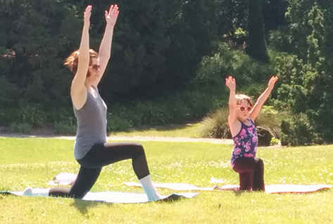 Woman and child in sunglasses doing yoga in the gardens